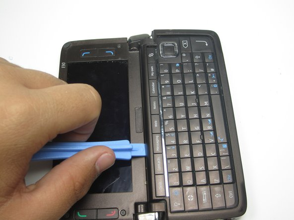 Open the phone up and use the plastic opening tool to remove the cover to the keyboard.