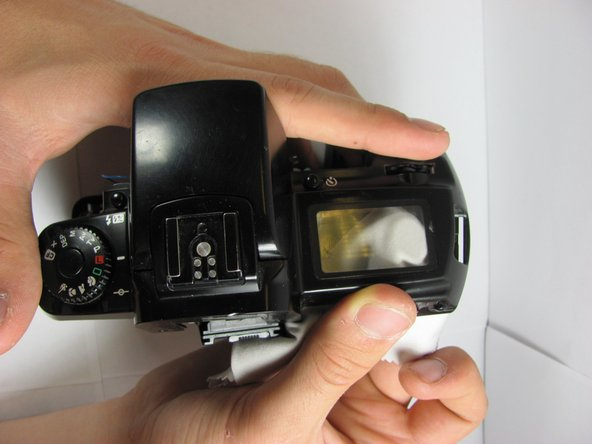 Use a soft cloth to push up on the LCD plastic protector from underneath the top of the camera.