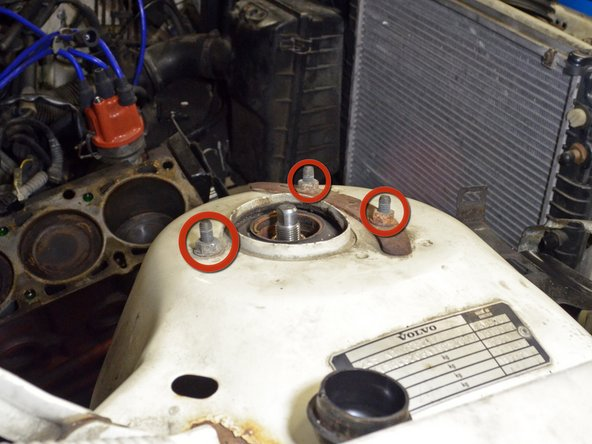 Open the hood and locate the three strut mounting bolts on the strut tower.