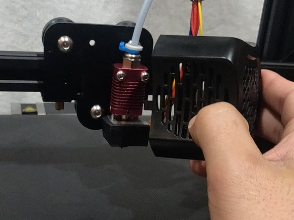 Remove the shroud to reveal the hot end of the 3D printer. Remove the shroud by pulling straight away from the hot end of the 3D printer.