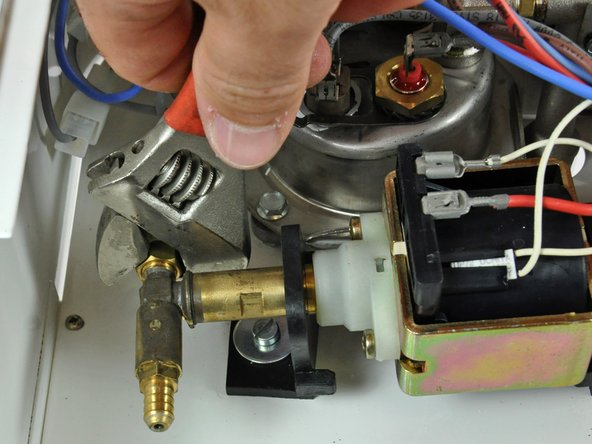 Use a wrench to remove the boiler hose from the pressure release valve.