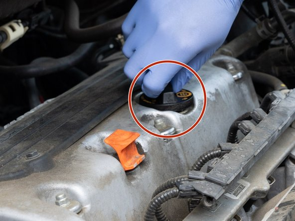 Let the vehicle cool for 15 minutes if needed.  Clean the area around the oil cap.  Remove the oil cap.