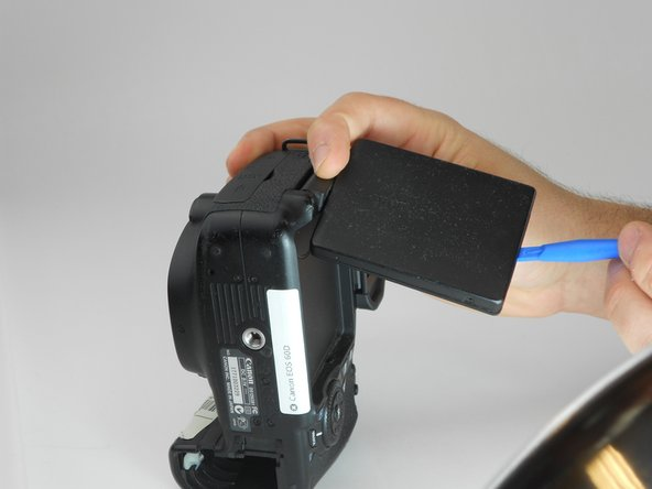 Using a plastic opening tool, carefully pry off the back cover of the LCD.