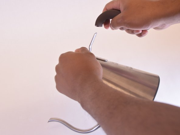 Detach the handle by sliding it off the metal arm of the coffee pot.