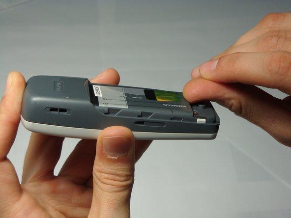 À l'aide de votre ongle, tirez l'arrière de la batterie vers le haut et retirez-la.