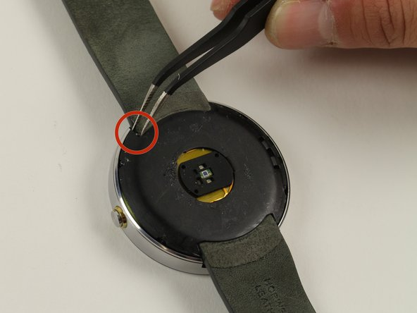 Locate the spring-loaded pin that attaches the wrist strap to the watch.