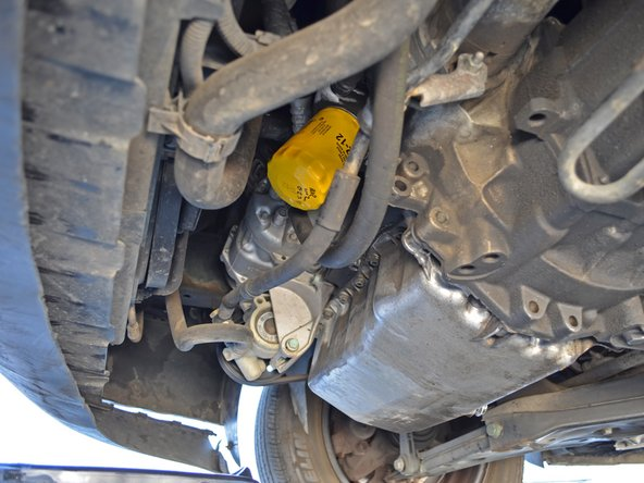 Locate the oil filter on the front side of the engine. It should be pointing downward and slightly forward.