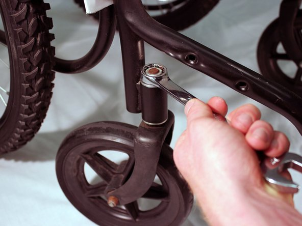 Use the socket head of the 19mm wrench to unscrew the nut that connects the castor wheel's fork to the steel frame.