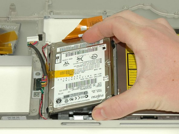 Lift the hard drive up from the right side and remove it from the computer.