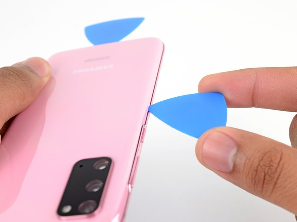 Once the pick is underneath the glass's edge, tilt it downward and insert it further to fully separate the back cover's adhesive.