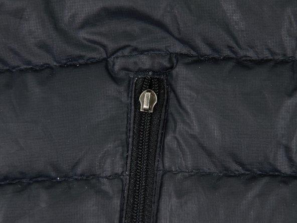 Den Reißverschlussanhänger nehmen und die Kordel durch das Loch des Schiebers fädeln, wo vorher der Schiebergriff war.