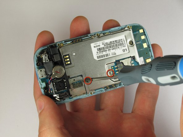 Loosen the two captive screws on the metal plate near the center of the phone using the Phillips #0 Screwdriver.