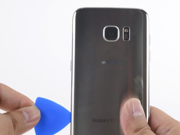 Slide the opening pick up along the side of the phone, separating the adhesive.