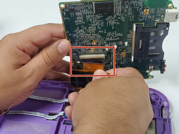 Lift the motherboard up to expose the fourth ribbon cable underneath.