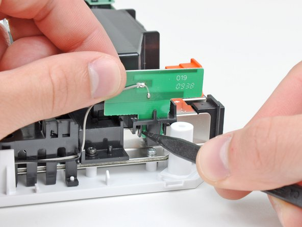 Use the tip of a spudger or another fine-pointed tool to carefully pry one of the black plastic retaining fingers attached to the fan shroud away from the Wi-Fi antenna board.