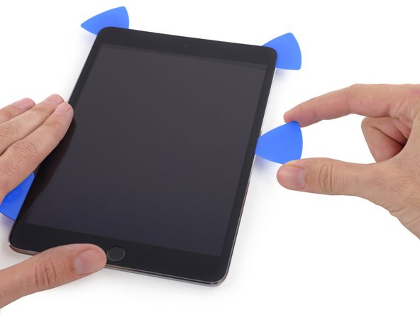 Continue to slide the pick down the right edge of the iPad, releasing the adhesive.