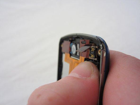 Un-clasp the small tab in the top right corner.