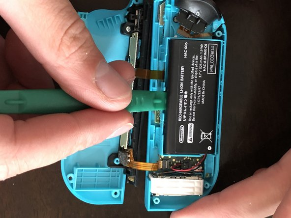 Insert a spudger or plastic opening tool underneath the battery and gently begin prying downward to release the adhesive holding the battery in place.