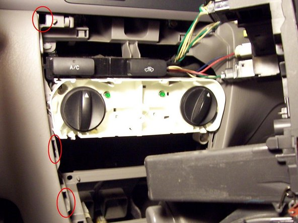 You'll need to carefully pull the whole instrument cluster out of the dashboard. The plastic clips circled in red are what is holding it in, so carefully pry there. A putty knife or other thin blade may help.