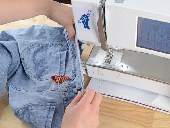 Slide the jeans into the sewing machine, positioning the needle over the edge of the patch.