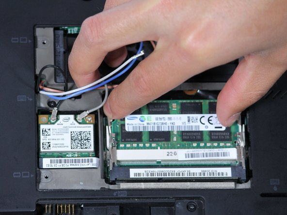 Push the metal clips away from the RAM.