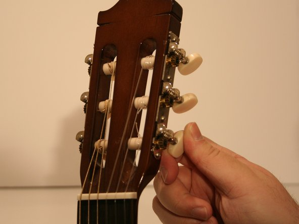Turn the tuning pegs counter clock-wise to loosen all of the guitar strings.
