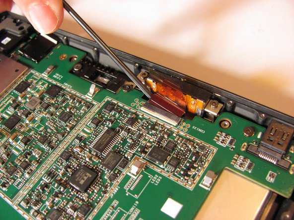 Using tweezers, gently pull the eight orange ribbon cables from their sockets.