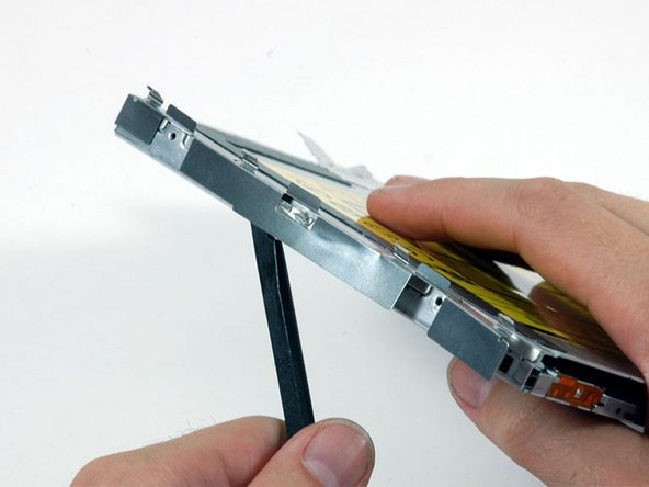 Use a spudger to carefully pry the silver metal bracket off the left side of the optical drive. Be careful not to bend the bracket, as it is very thin and bends easily. If the bracket doesn't come free easily, heating the adhesive may make prying the bracket off easier.
