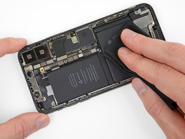 Press the battery firmly onto the adhesive strips to secure it in place.