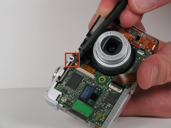 Use the flat end of the spudger to lift open the white plastic latch on the front of the camera. Once the latch is lifted up, move the latch up towards the top edge of the camera.