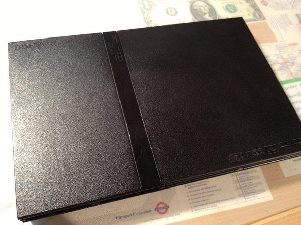 Sobre una superficie plana, dale la vuelta a tu PlayStation 2 Slimline de forma que la parte inferior esté hacia arriba.