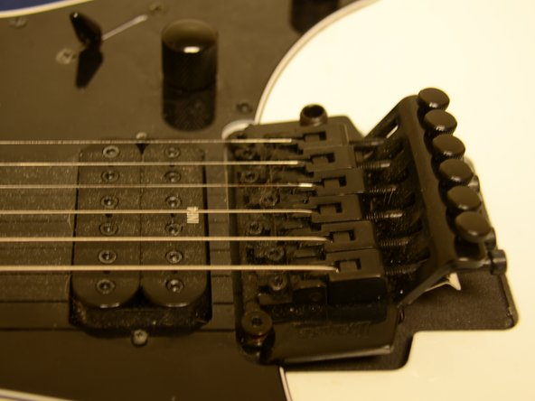 Examine the bridge of the guitar to see if it is currently balanced.