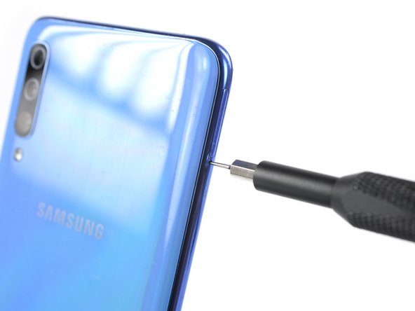 Insert a SIM card eject tool, a SIM eject bit, or a straightened paper clip into the hole on the SIM tray located at the left edge of the phone.