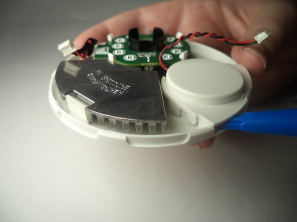 Insert plastic opening tool below the plastic speaker cover on the inside of the removed front panel of the device.