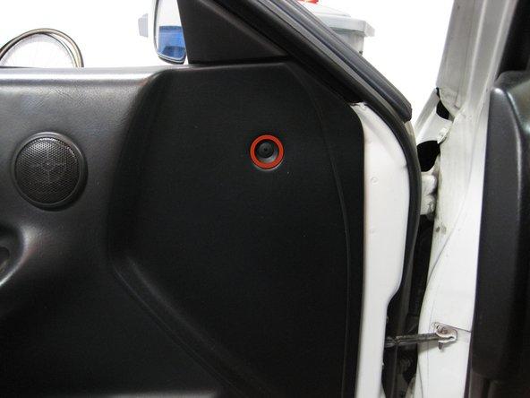 Remove the plastic Phillips screw towards the front of the door panel.