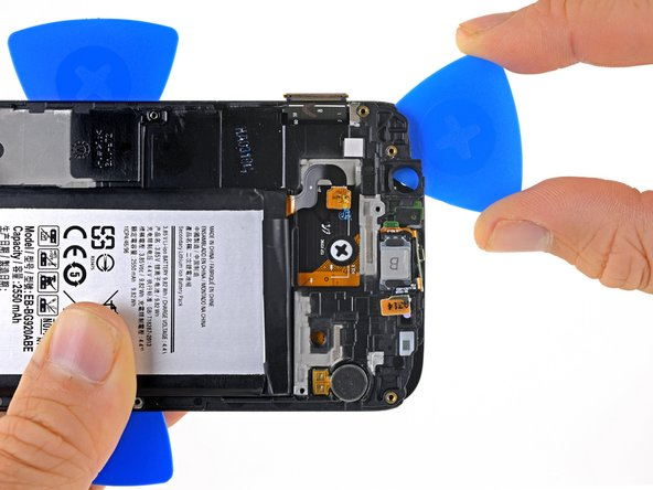 Slide a pick along the top of the phone towards the vibrator.