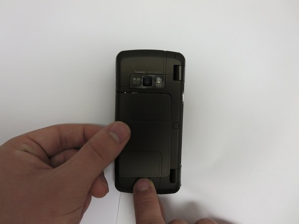 Slide the release latch down and toward you while lifting up on the left side of the battery cover.