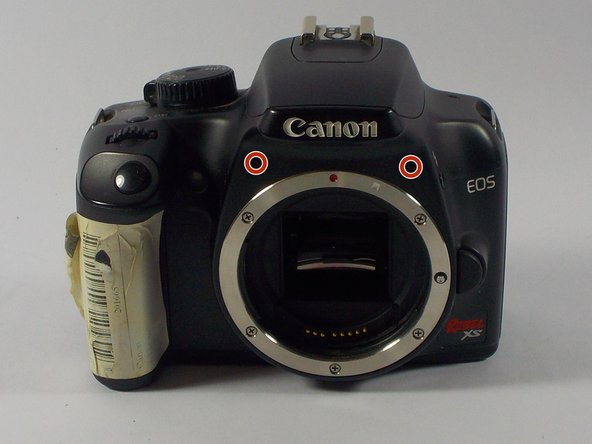 Remove the two medium length screws on the front panel of the camera above the lens mount.