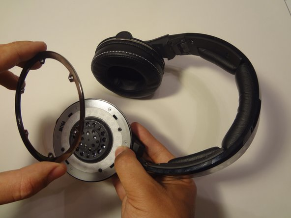Using your screw driver, remove the six Philips 2mm screws located on the chrome ring.