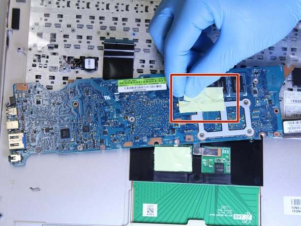 Lift gently and flip the motherboard over in the direction of the track pad.