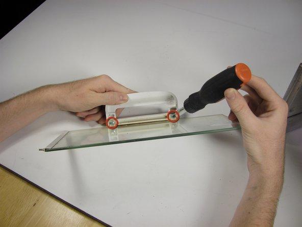 Unscrew the two door-handle screws.