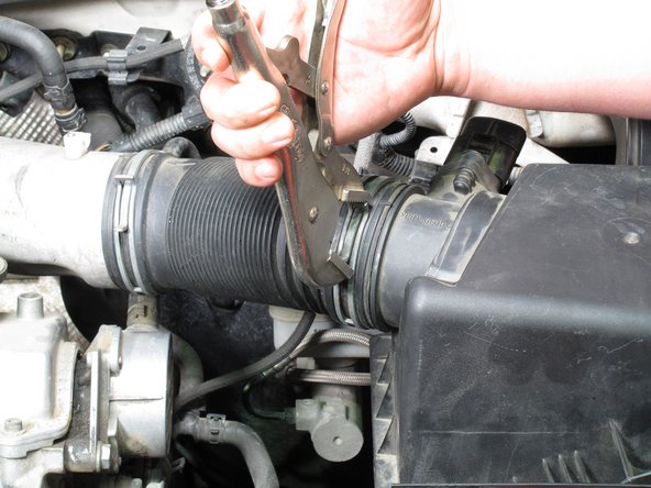 Using a vise grip, grip the metal ring securing the intake tube to the air filter cover.