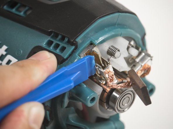 Use the plastic opening tool to release the clip connected to the drill brush.