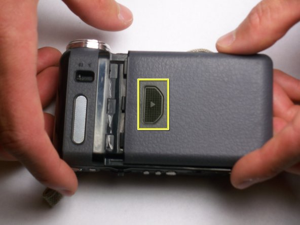 On the back of the camcorder, the side opposite of the flip-out screen, there is a section of grooved plastic with a small arrow.