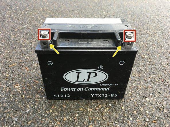 An der Batterie können nun die Schrauben mit einem Schraubenzieher PH 3 ( alternativ können auch ein Gabelschlüssel oder ein Steckschlüssel Gr. 10 verwendet werden) entfernt werden.