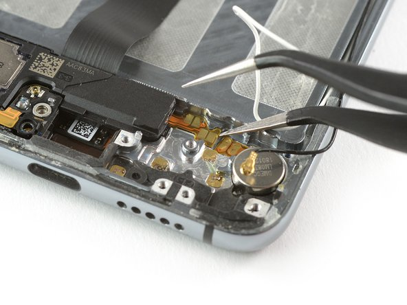 Use one arm of a pair of tweezers to peel up the contact cable of the loudspeaker.