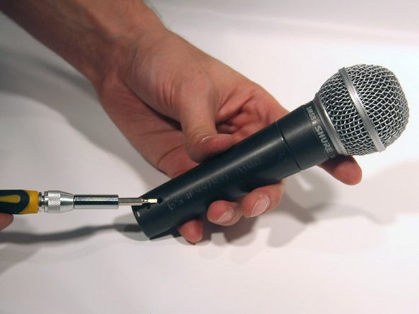 Using a small flat head screwdriver, gently turn the retaining screw at the bottom of the microphone counterclockwise until it stops or provides resistance.