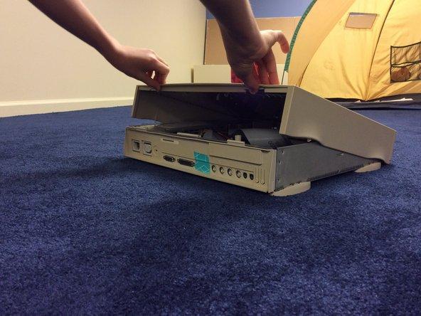 Para empezar, levanta las dos pestañas en la parte trasera del ordenador y saca la cubierta.