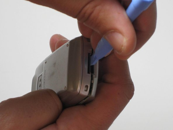 Slide the opening device downward to dis-join the rear casing from the front casing. Continue around all edges.