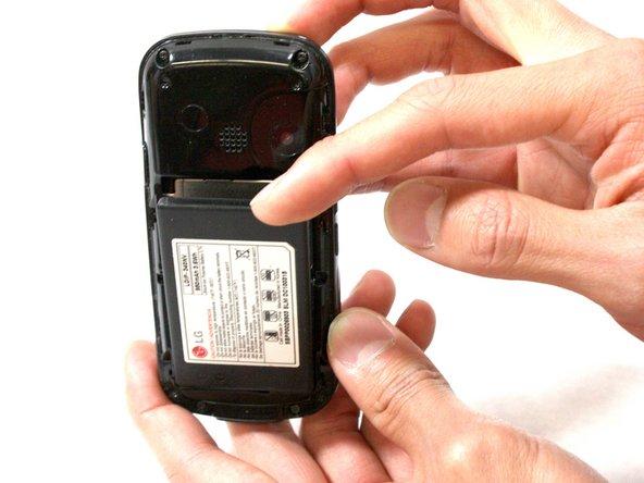 Utilisez votre doigt pour pousser sur le dessus de la batterie et retirez-le.